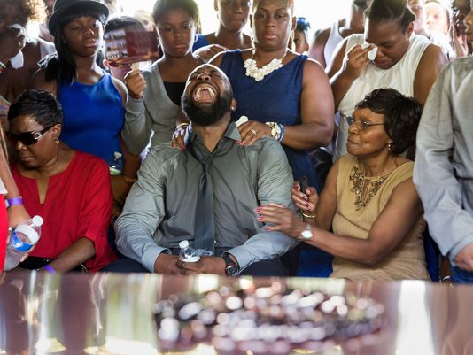 Michael Brown Sr. (center), surrounding by family at the grave site where his son was laid to rest.