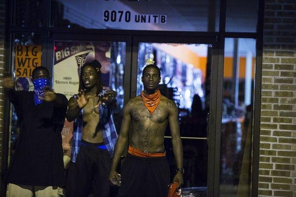 Ferguson protestors preventing the looting of businesses last night. Photo: Twitter/@KhaledBeydoun